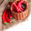 Red hot chili peppers in wicker basket,on sackcloth, isolated on white — Stock Photo #35998793