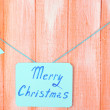 Signboard with words Merry Christmas on orange wooden table background close-up — Stock Photo