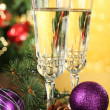Composition with Christmas decorations and two champagne glasses, on bright background — Stock Photo #35998955