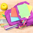 Purple backpack with school supplies on wooden background — Stock Photo #35999967