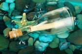Bottle with letter on sea bottom with shells and stones — Stock Photo