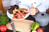 Cocinar las manos sosteniendo el plato en el lugar de trabajo — Foto de Stock