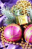 Beautiful Christmas decor on purple satin cloth — Stockfoto