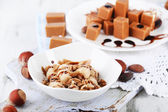 Many toffee on plate and in bowl on napkin on board on wooden table — Stock Photo