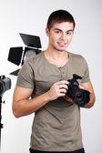 Красивый фотограф с камерой, на фоне студии фото — Стоковое фото