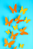 Paper butterflies on blue wooden board background — Stock Photo