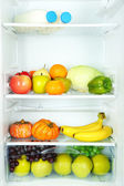 Milk bottles, vegetables and fruits in open refrigerator. Weight loss diet concept. — Stockfoto