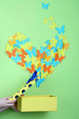 Paper butterflies fly out of box on green wall background — Foto de Stock