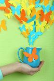 Papíru motýli létají ze džbánu na pozadí zelené zdi — Stock fotografie
