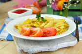 Ruddy fried potatoes on plate on wooden table close-up — Stockfoto