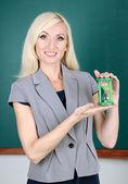 School teacher near table on blackboard background — Stock Photo