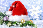 Composition with Santa Claus red hat and Christmas decorations on light background — Stok fotoğraf