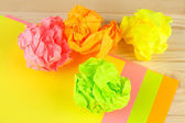 Colorful crumpled paper balls on wooden background — Stock Photo