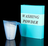 Box of washing powder with blue measuring cup, isolated on black — Stock Photo