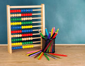 Toy abacus and pencils on table, on school desk background — Stock Photo