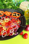 Vegetables in wok on wooden table on natural background — Stock Photo