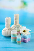 Aromatic salts in glass bottles and herbal compress balls for spa treatment, on blue background — Stock Photo