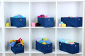 Blue textile boxes with yarn in white shelves — Stock Photo