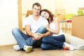 Jovem casal com caixas em nova casa no fundo da sala — Fotografia Stock