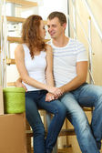 Young couple sitting on stairs in new house — Stok fotoğraf