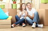 Genç bir çift yeni evde oturan kutuları arasında taşıma kutluyor — Stok fotoğraf