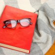 Stock Photo: Composition with old book, eye glasses and plaid on wooden background