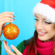 Beautiful smiling girl with Christmas ball on blue background — Stock Photo #36000157