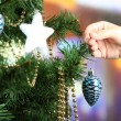 Decorating Christmas tree on bright background — Stock Photo #36000327