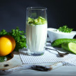 Cucumber yogurt in glass, on color napkin, on wooden  background — Стоковая фотография