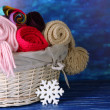 Warm knitted scarves in basket on wooden table on blue background — Stock Photo
