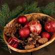 Christmas decorations in basket and spruce branches on wooden background — Stock Photo #36001981