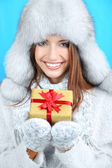 Beautiful smiling girl in hat with gift on blue background — Stock Photo