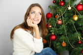 Beautiful smiling girl sitting near Christmas tree in room — Foto Stock