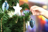 Decorating Christmas tree on bright background — Stok fotoğraf