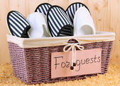 Slippers in basket on carpet on wooden background — Stock Photo