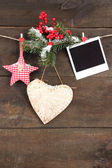 Decorative heart, star and empty photo paper on rope, on wooden background — Stok fotoğraf