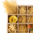 Nine types of pasta in wooden box sections isolated on white — Stock Photo #36116077
