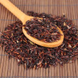 Stock Photo: Black rice in wooden spoon on bamboo mat