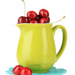 Ripe red cherry berries in pitcher isolated on white — Stock Photo
