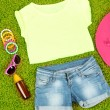 Top, shorts and beach items on bright green background — Stock Photo #36119059