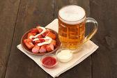 Cerveja e salsichas grelhadas sobre fundo de madeira — Foto Stock