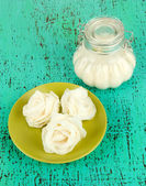 Sugar roses, glass jar with sugar, on color background — Stock Photo