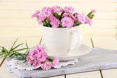 Many small pink cloves in cup on wooden board on beige background — Stock Photo