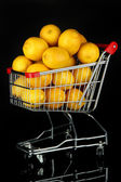 Ripe lemons in trolley isolated on black — Stockfoto