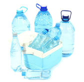 Water in different bottles in cooling bag isolated on white — Stock Photo