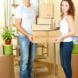 Stock Photo: Young couple with boxes in new home on staircase background