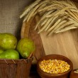 Stock Photo: Pears in basket and bowls of grains with wooden tub on shelf on sackcloth background