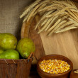 Pears in basket and bowls of grains with wooden tub on shelf on sackcloth background — Stock Photo