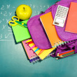 Purple backpack with school supplies on green desk background — Stock Photo #36122867
