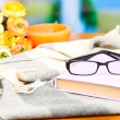 Stock Photo: Composition with old book, eye glasses, candles, flowers and plaid on bright background